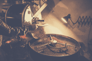 coffee roaster roasting coffee beans with a commercial coffee roaster