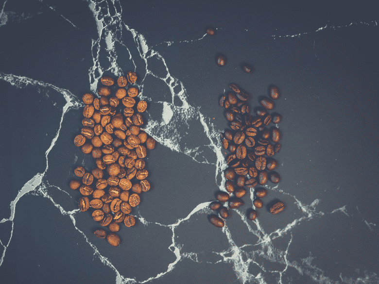 two types of coffee beans on a black surface, how much caffeine is in your coffee