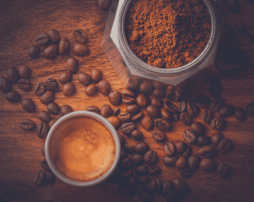 coffee beans on surface, a mug of coffee ground, and a cup of espresso