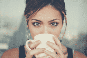a close up picture of a lady in sleeveless drinking a cup of coffee