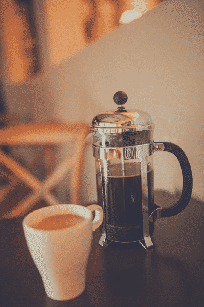 french press with a cup of brewed coffee