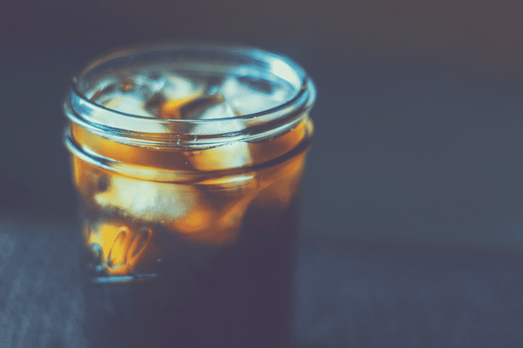 black coffee with ice cubes in mason jar