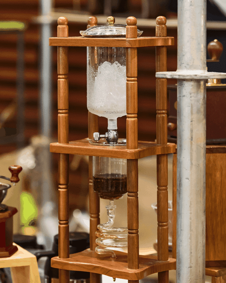 cold drip coffee brewer held up by a wooden cage