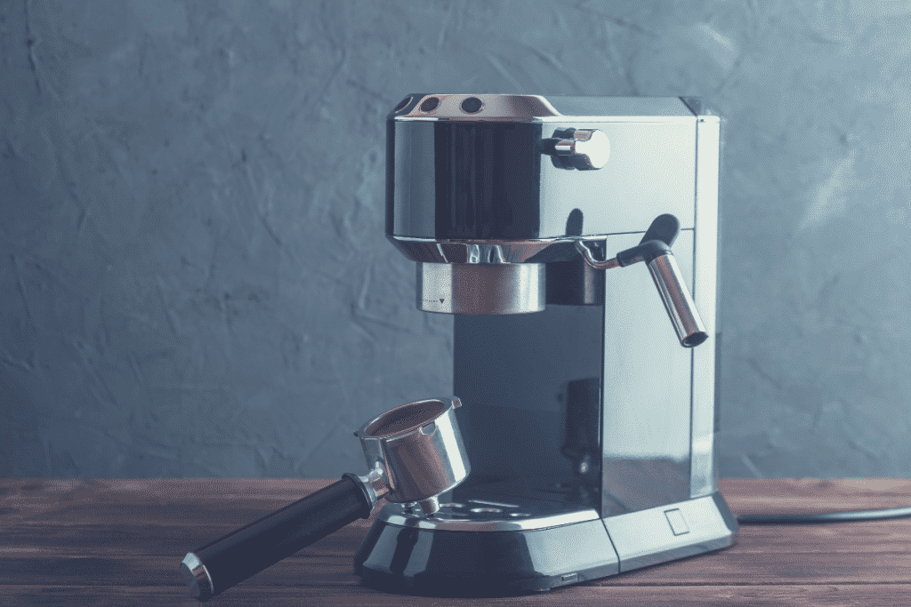 small espresso machine on a table surface with a full portafilter filled with ground coffee, best espresso machine under $100