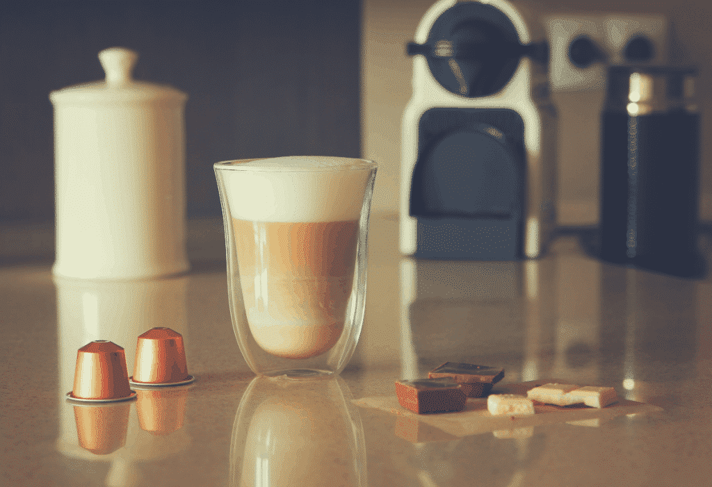 a shot of latte with pods and chocolate in the foreground, nespresso and frother at the background, best coffee makers for single person
