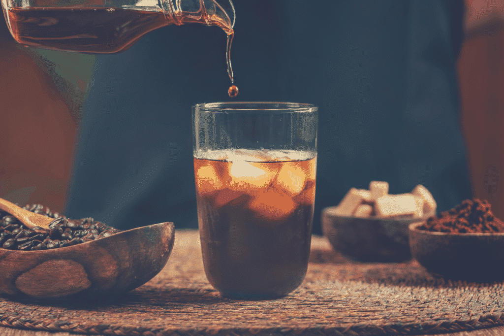 a man pouring a glass of cold brew coffee, does cold brew have more caffeine than iced coffee