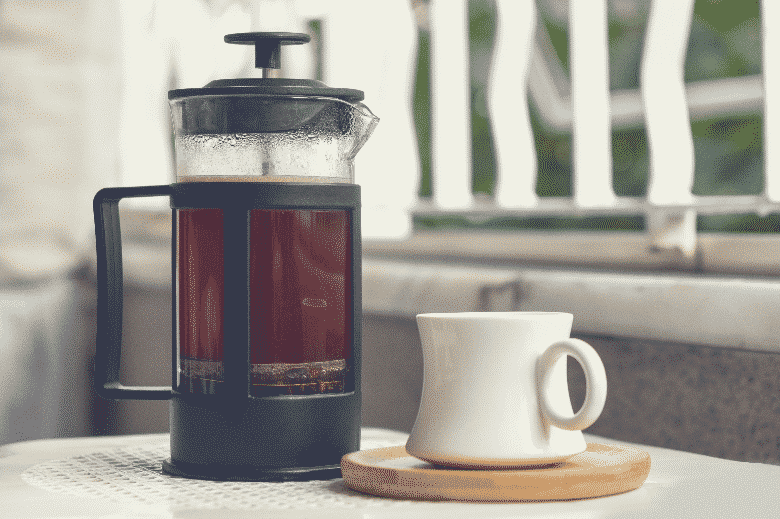 Cup of coffee made with French press on the white table, how to brew coffee without a coffee maker