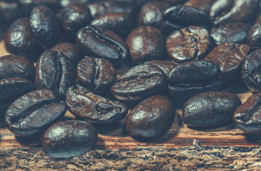 dark roast coffee beans on brown wooden surface
