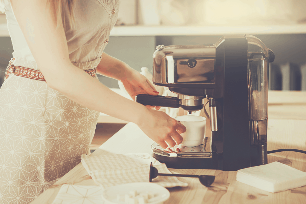 Woman making fresh espresso in coffee maker. coffee machine makes coffee