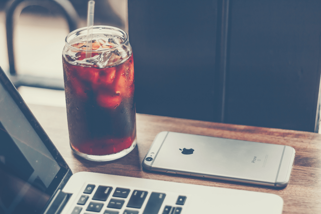 glass of cold brew coffee beside a Macbook Pro and Iphone, how to make cold brew coffee fast