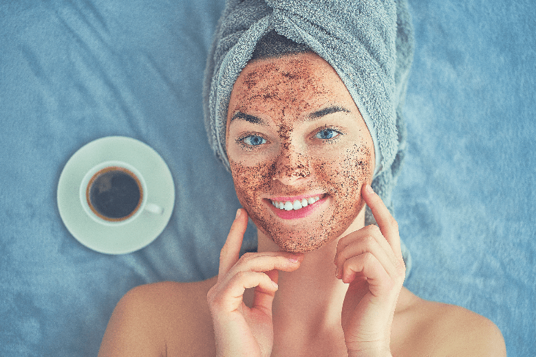 Portrait of smiling healthy woman in bath towel with natural cleansing face coffee scrub during spa day and skin care routine at home, uses of coffee grounds