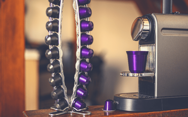 silver and purple coffee capsules on a trophy beside a coffee machine, best nespresso pods