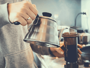 a man pouring hot water with a gooseneck kettle over aeropress