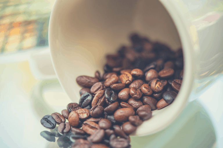 coffee beans spilling out from a white ceramic cup