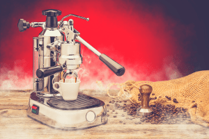 professional manual silver coffee machine with cup of coffee, stamper and sack coffee beans on red background, product protography for coffee shop, manual espresso machine