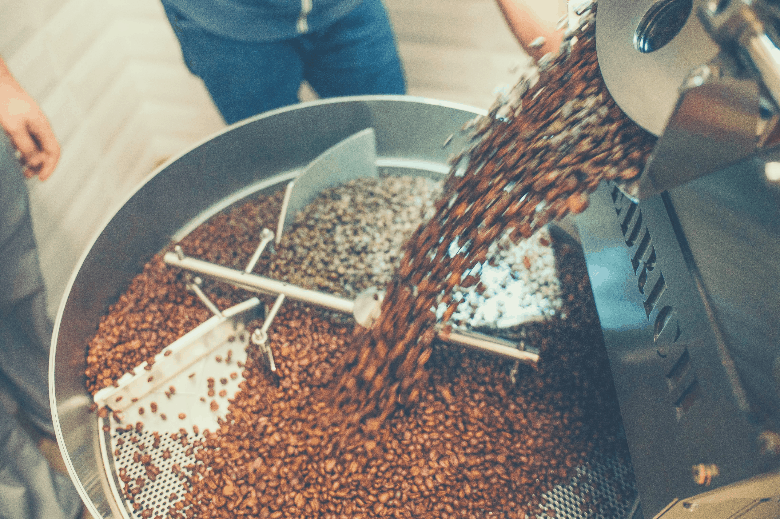 coffee roasting machine pouring coffee beans into mixing container, coffee container
