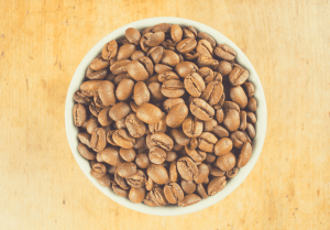 Light roast brown coffee beans in a white bowl on a wooden table top