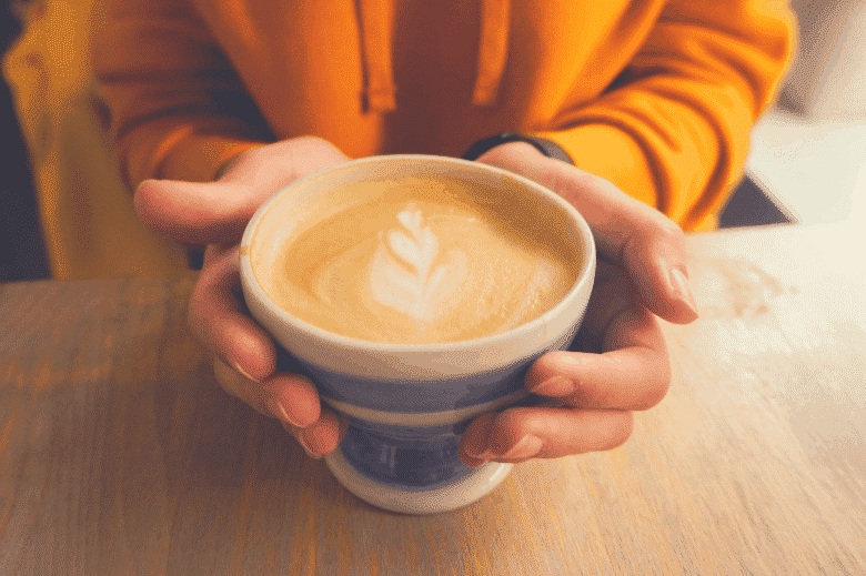 a woman holding a white ceramic cup of latte, latte vs mocha