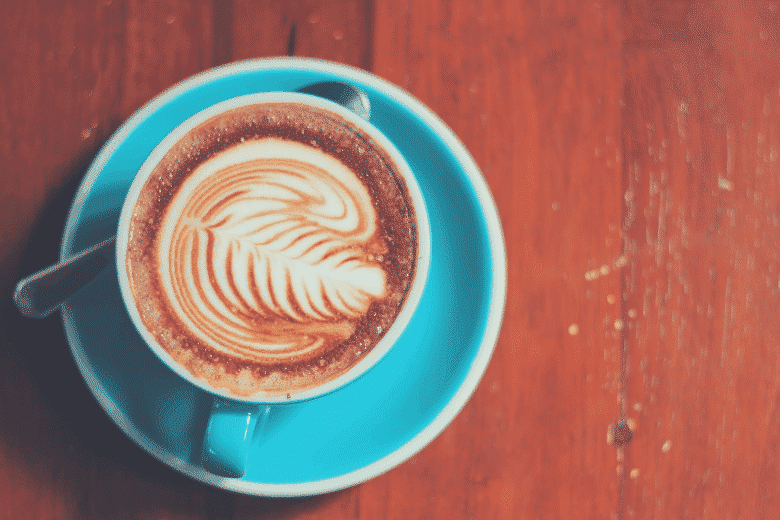 a blue ceramic cup of mocha on a wooden table, starbucks latte