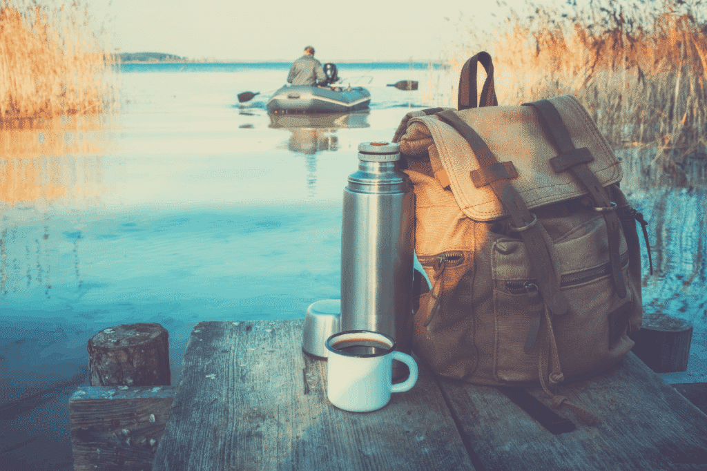 Enameled mug of coffee or tea, backpack of traveller and thermos on wooden pier on tranquil lake. A fisherman on rubber boat in background