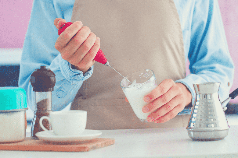 Woman in apron making coffee with using a milk frother at kitchen at home, best milk frother