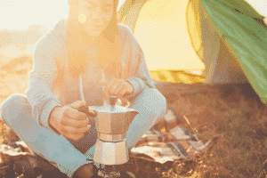 Young traveler woman making coffee outdoors near a tent