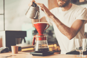 Close up photo of barista at bar counter preparing coffee in pour over and hario style while working in cafe