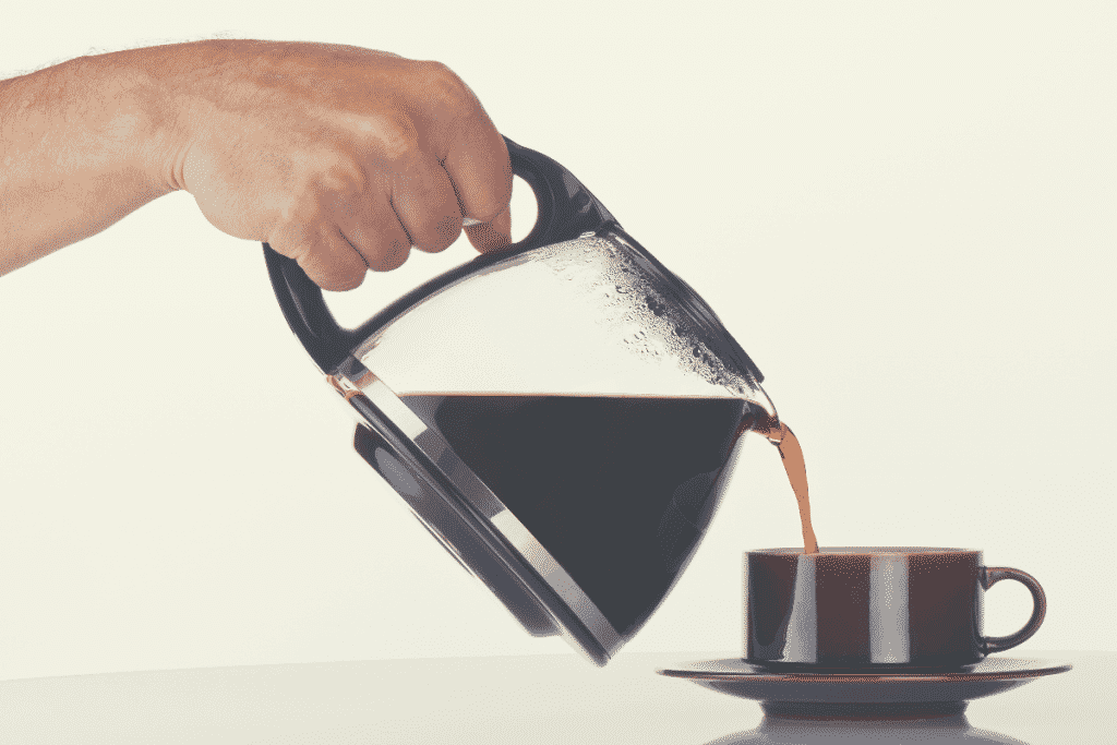 man's hand holding and pouring coffee into a brown cup, ninja coffee bar
