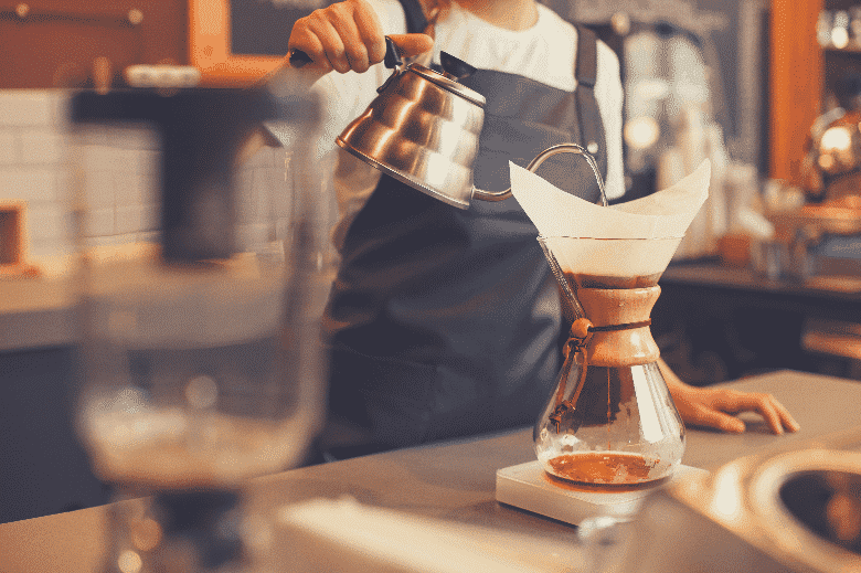Professional barista preparing coffee using chemex pour over coffee maker and drip kettle. Young woman making coffee. Alternative ways of brewing coffee. Coffee shop concept, chemex coffee maker