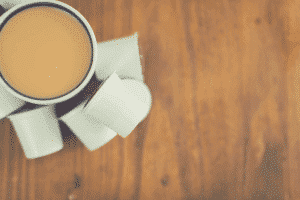 cup of coffee and pods on wooden table