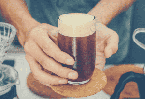 Barista holding and serving nitro cold brew coffee