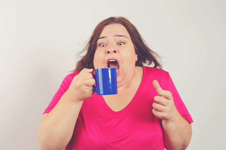a woman holding a cup of coffee grimacing on the intense coffee, match head in coffee
