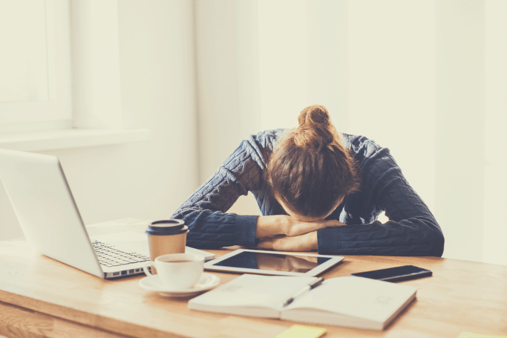 Tired and overworked business woman. Young exhausted girl sleeping on table during her work using laptop, digital tablet and smartphone. Entrepreneur, freelance worker or student in stress concept, why coffee makes you sleepy