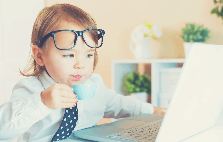 Smart toddler girl with glasses drinking coffee while using a laptop, can coffee stunt your growth
