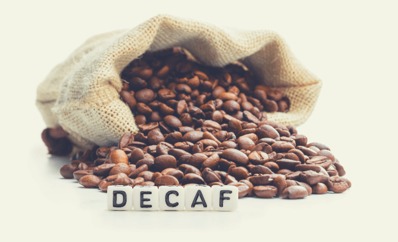 Roasted coffee beans scattered out of the bag. Concept of decaf coffee, why coffee is better than tea