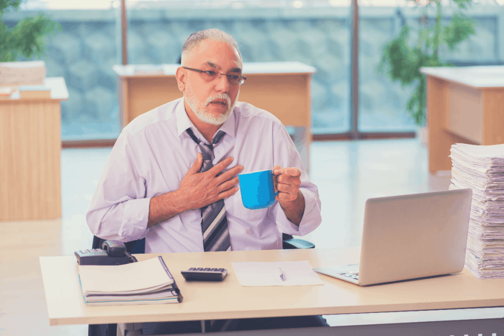 Aged businessman employee unhappy with excessive work, can coffee cause heartburn