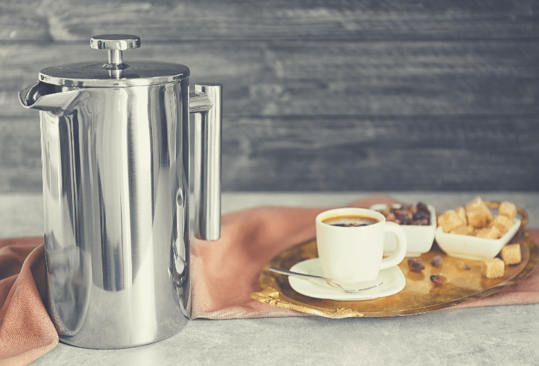 New coffee maker and cup of fresh drink on wall background, how to clean a stainless steel coffee percolator
