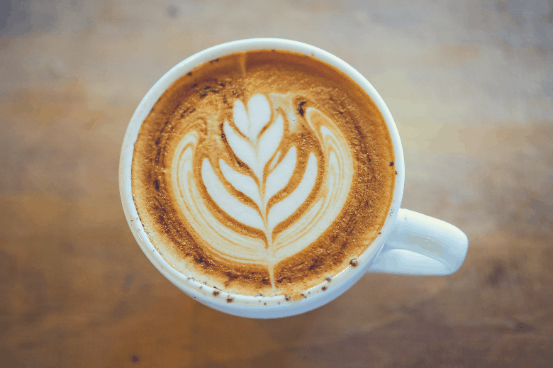 Hot Cappuccino with white cup on wood table coffee house, how to make coffee art with milk