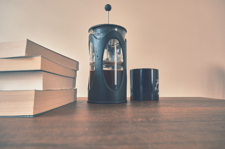 french press coffee maker and it is half filled with arabic and black coffee together with black coffee pot with bundle of a books. All things standing on wooden table