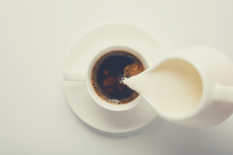 top view of cup of coffee and jug of milk on white, milk in coffee maker