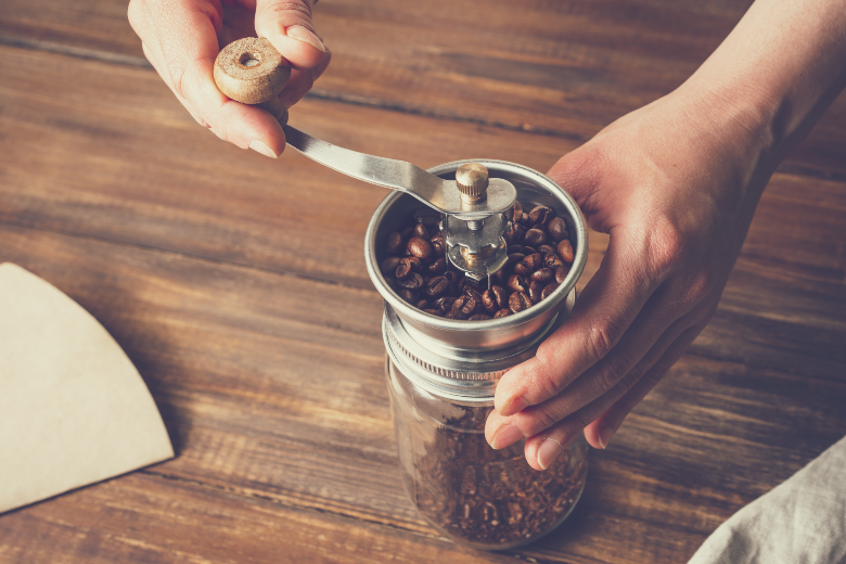 Grinding coffee beans in a manual coffee grinder on a wooden table, coffee grinder vs blender