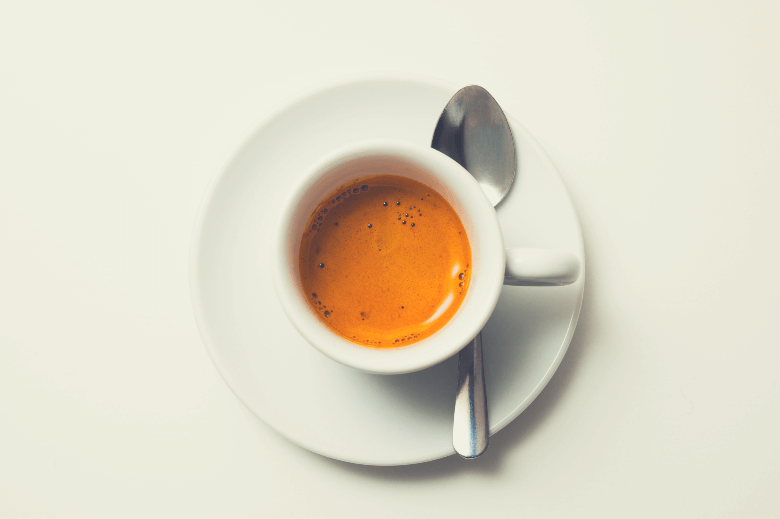 top view a cup of fresh espresso coffee, close-up, why is espresso served with a spoon
