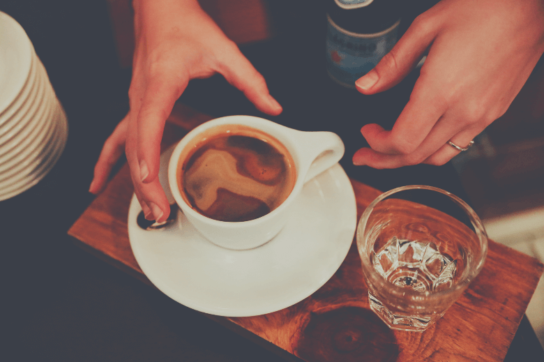 Closeup of female's fingers on a cup of coffee with sparkling water on a wooden tray, espresso served with sparkling water