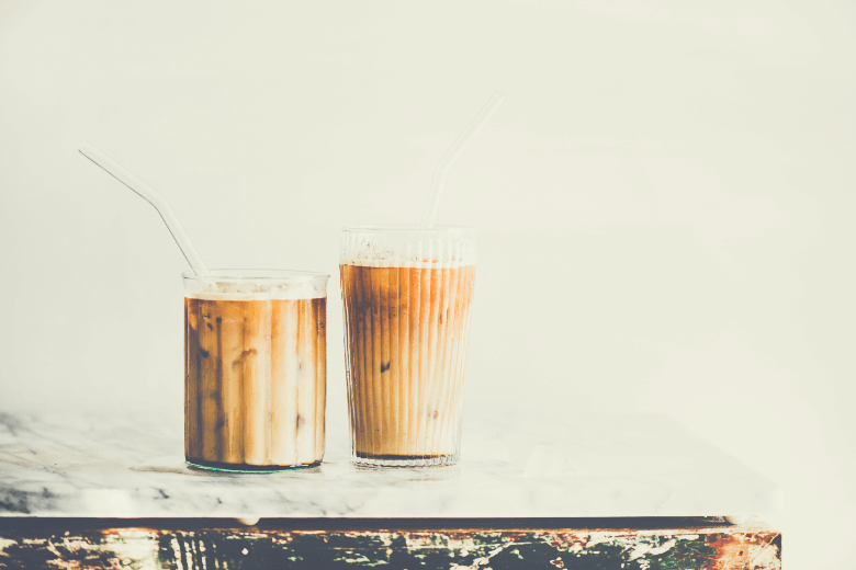 Homemade iced latte coffee in glasses with straws on grey marble table, white wall at background, copy space. Summer cold refreshing drink concept, iced vanilla latte vs iced caramel macchiato