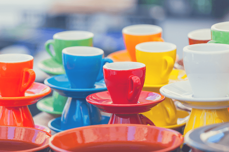 bright coffee cups of various colors on a show-window of shop, coffee cup vs mug