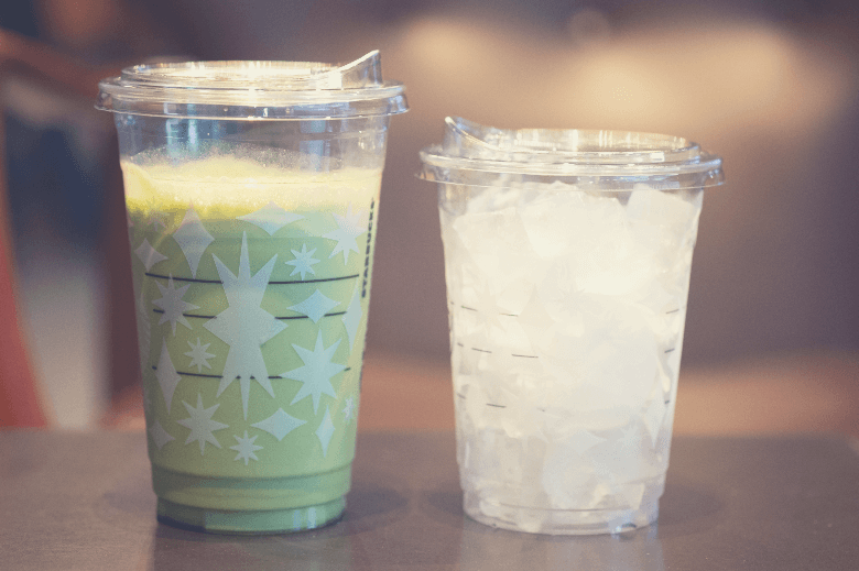 cup of iced green tea latte and ice in glass on wood table at Starbucks Coffee