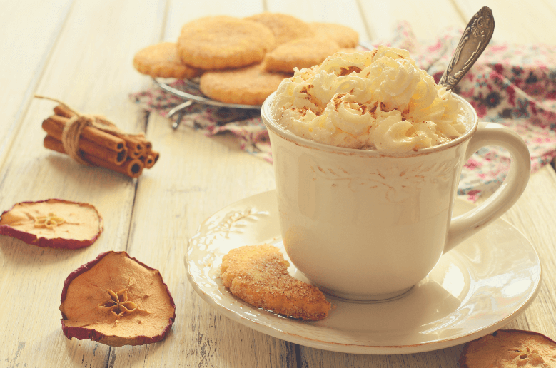 cup of whipped cream coffee and apple cookies on wooden table, can you use heavy whipping cream in coffee