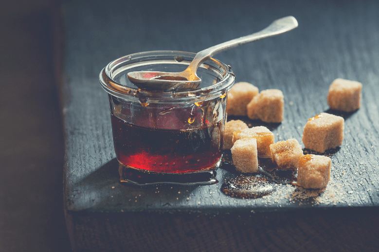 homemade liquid transparent brown sugar in a glass jar on a wooden board with a spoon and cubes of brown sugar, how to make brown sugar syrup