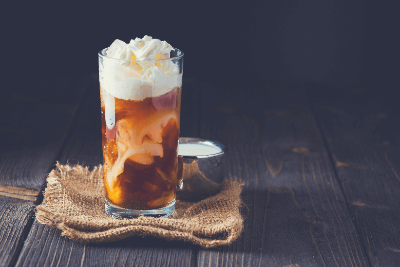 Iced coffee in a tall glass with cream poured over, how to make sweet cream cold foam