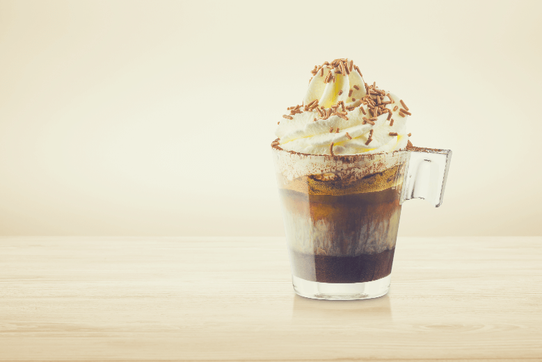 Cup of coffee with whipped cream, milk foam and chocolate chips on wooden table, starbucks whipped cream